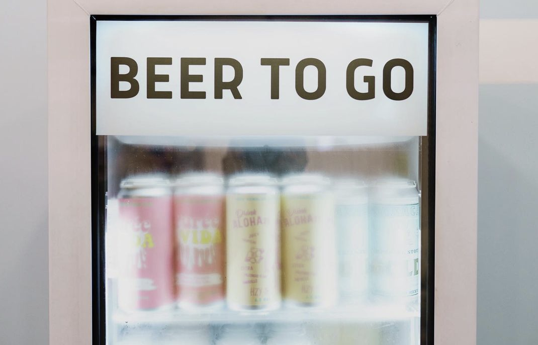 Refrigerator labeled 'beer to go' holds pastel colored beer cans for Boss Rambler Beer club in Bend Oregon