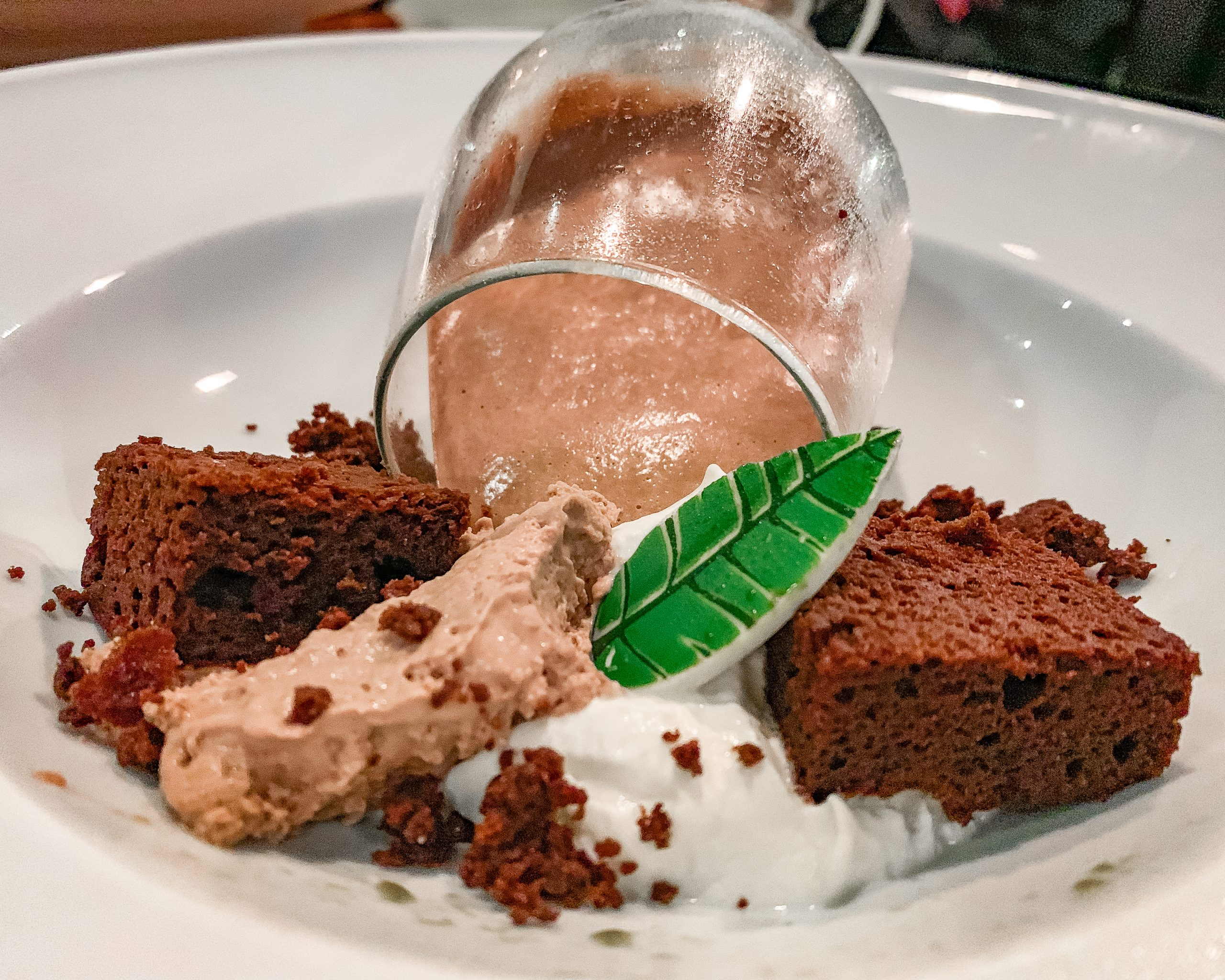 Cigar-Smoked chocolate Mousse Cake with dark chocolate basil semifreddo served in a wine glass.