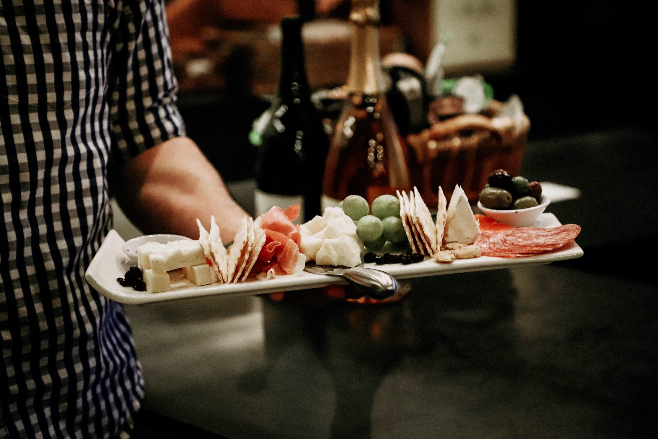 Man carries a charcuterie board to a table at Stoller Wine Bar Bend