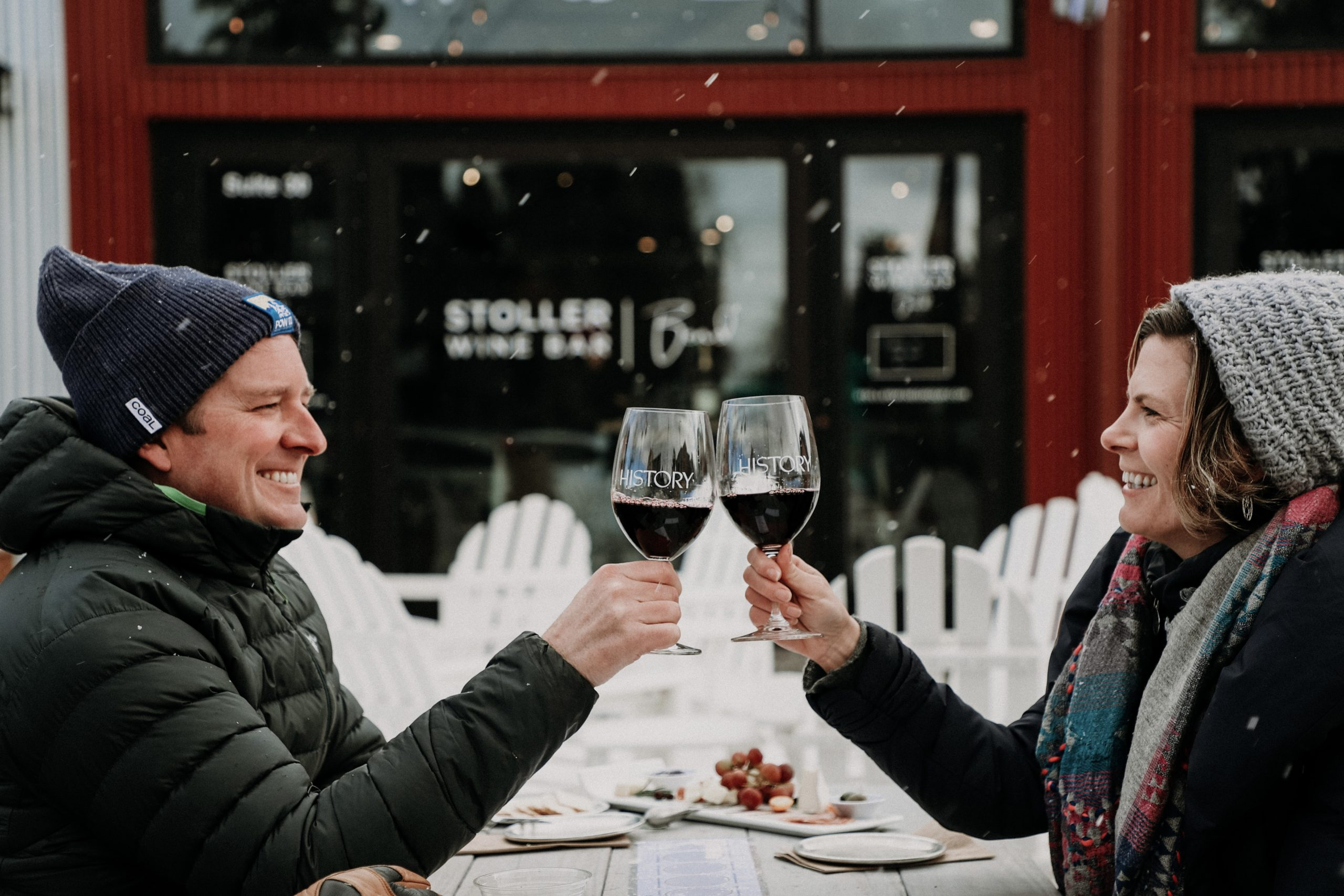 Man and woman cheers with a glass of red wine as snow falls outside of Stoller Wine Bar Bend patio
