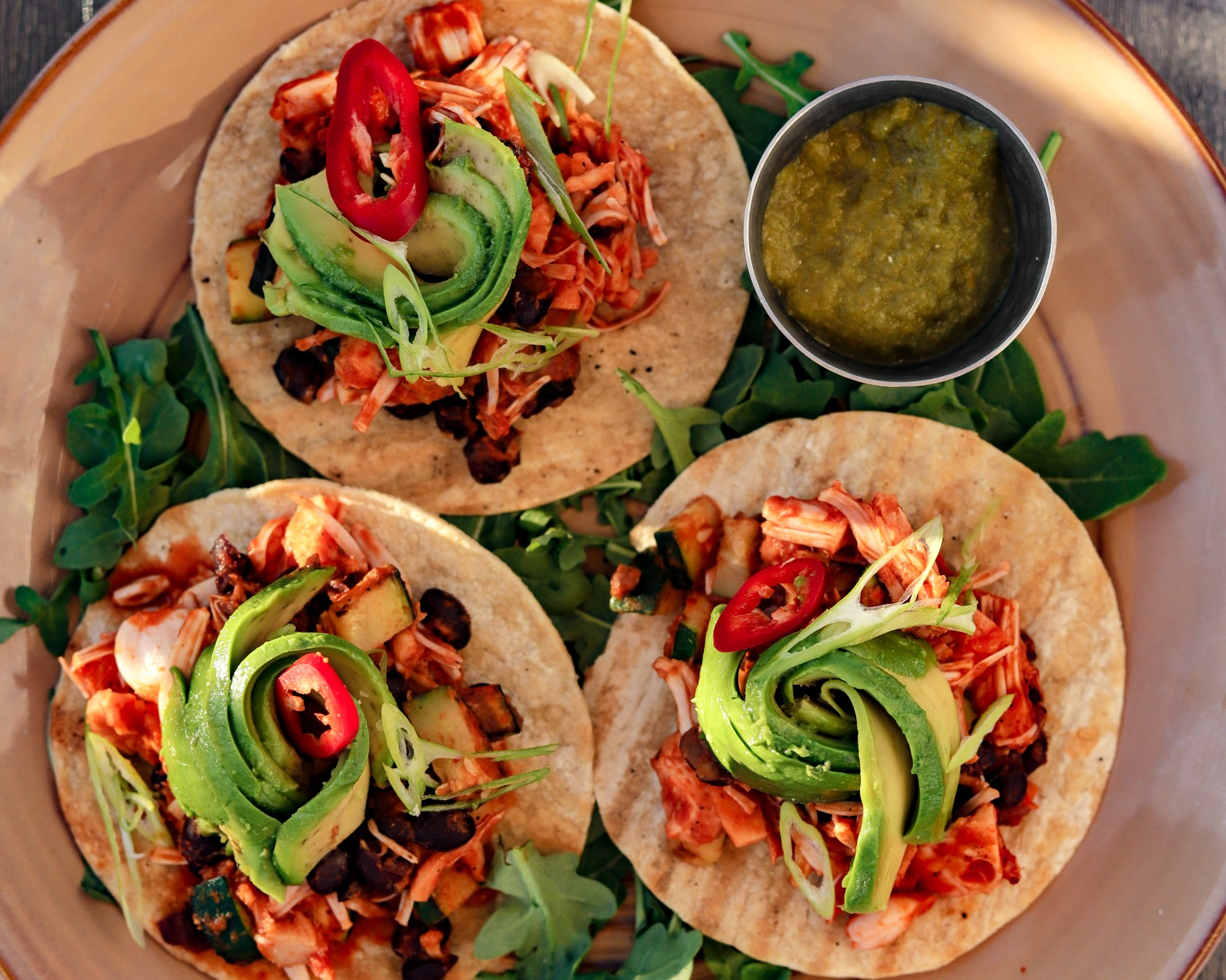 Plate of 3 tortillas topped with grilled jackfruit and bright green avocado arranged in a circular motion
