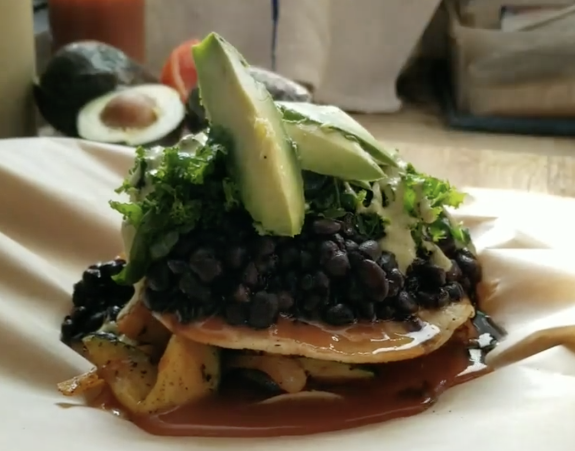 Crunchy layered enchilada is topped with black beans, avocado, and drizzled in a vegan cream sauce.