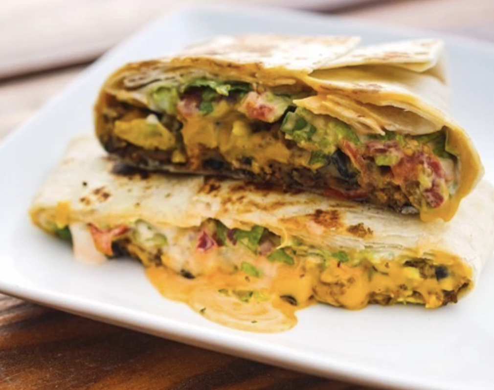 Vegan crunchwrap supreme is oozing with melted vegan cheese on a white plate on a picnic table