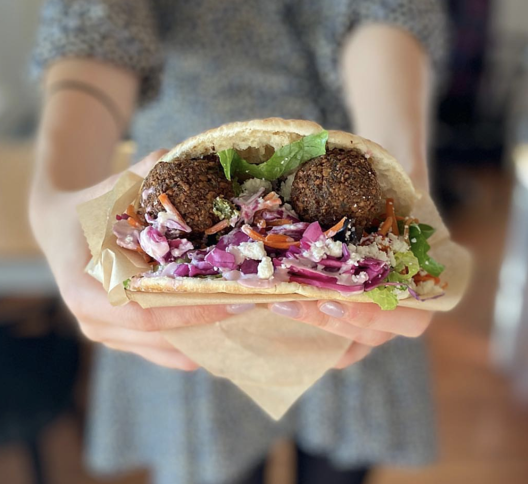 Woman holds a pita filled with falafel, pickled onion, feta cheese, and fresh greens
