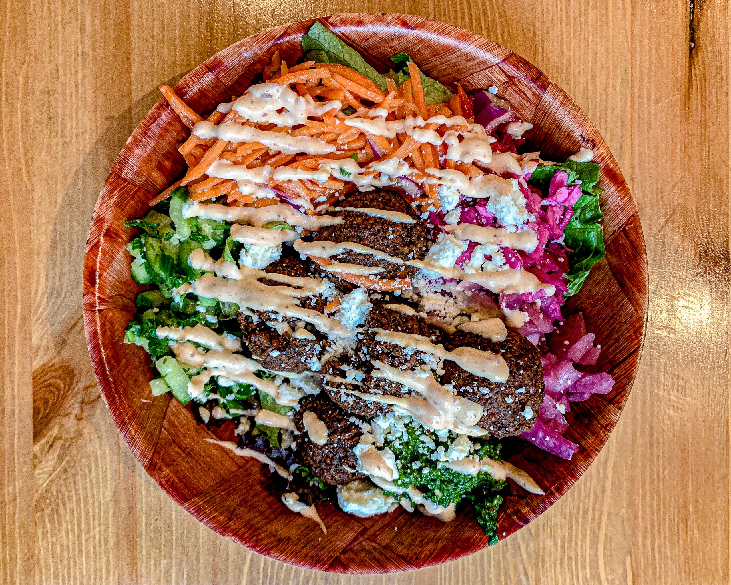 wooden bowl filled with fresh greens and topped with falafel and pickled purple cabbage, drizzled in bright orange and pink tahini sauces