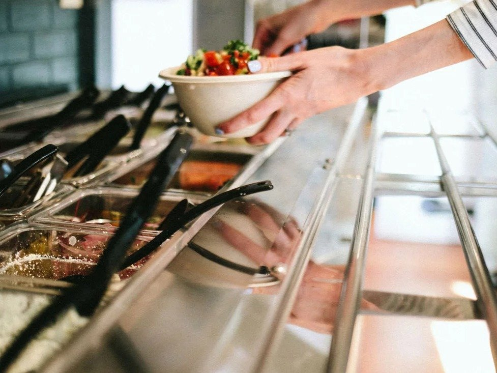 Woman fills a bowl with fresh tomato and salad standing in front of a salad bar.