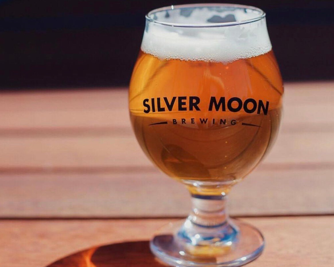 Chalis labeled silver moon brewing is filled with deep golden beer with a foamy top, sitting on a picnic table