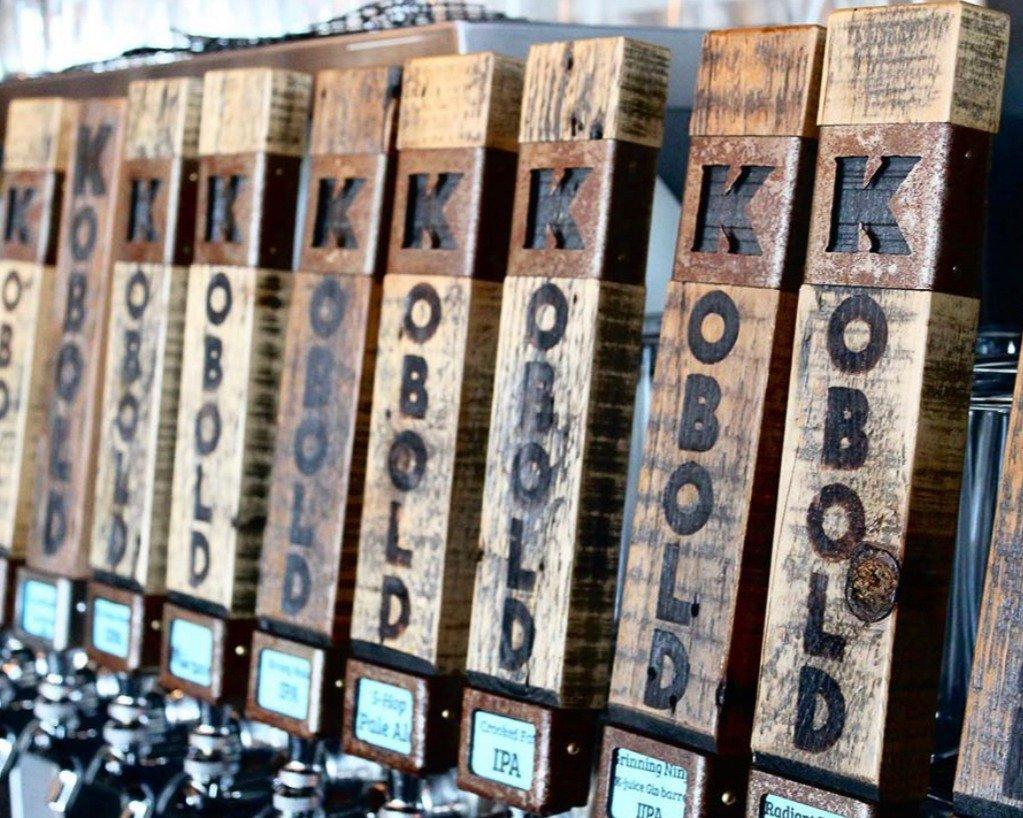 Several wooden keg taps are labeled Kobold