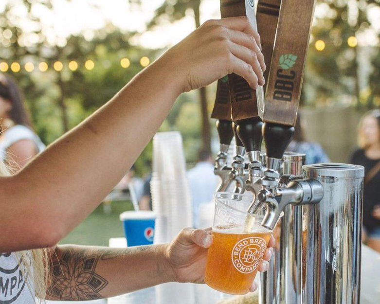 Woman pulls a keg tap pouring a golden colored beer in a plastic cup on a sunny day