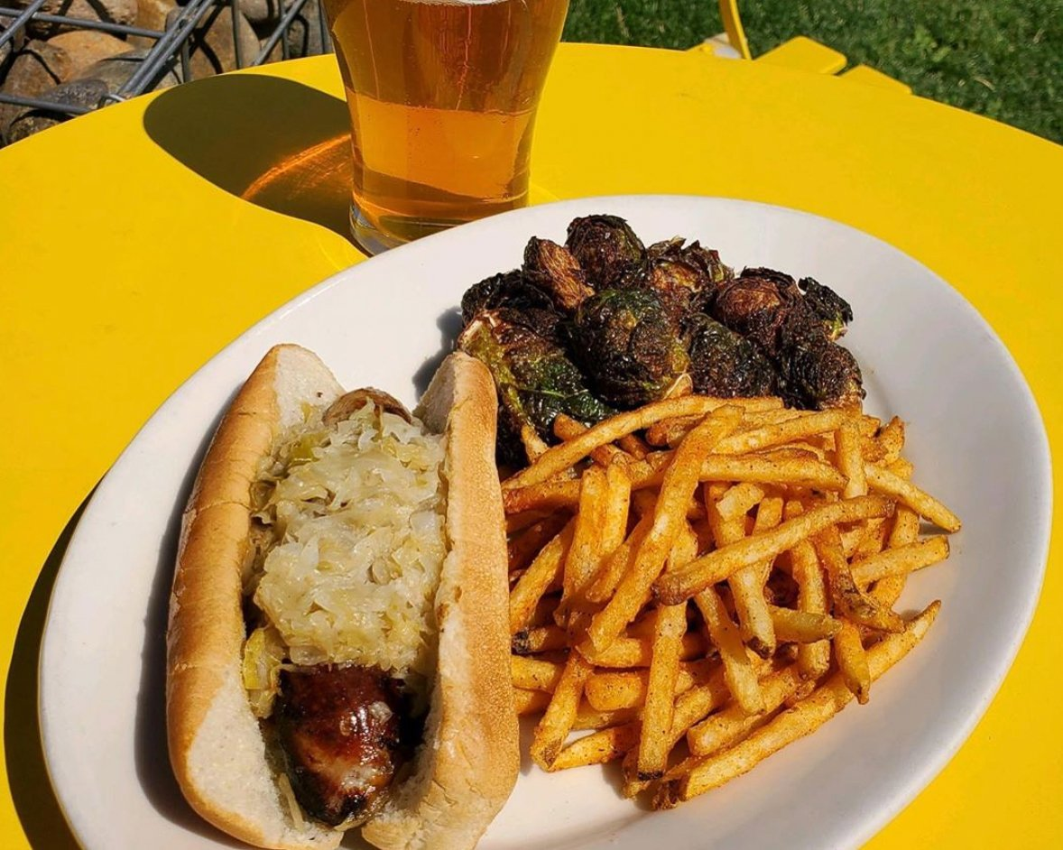 Plate of hotdog topped with sauerkraut, side of french fries, side of crispy brussel sprouts, sits on a bright yellow table