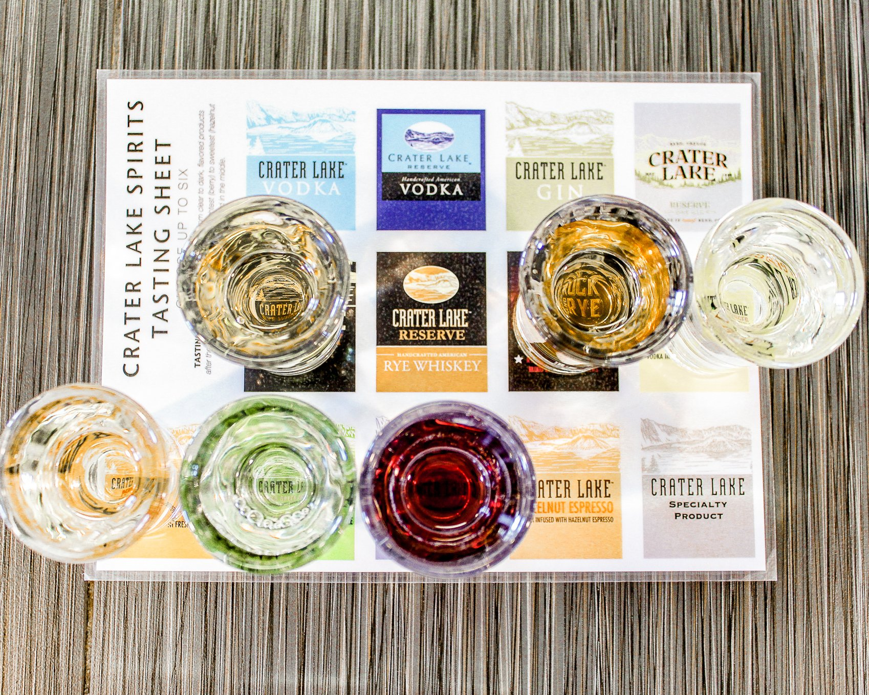 Shot glasses lined up on a menu with samples of Crater Lake Spirits flavored vodkas