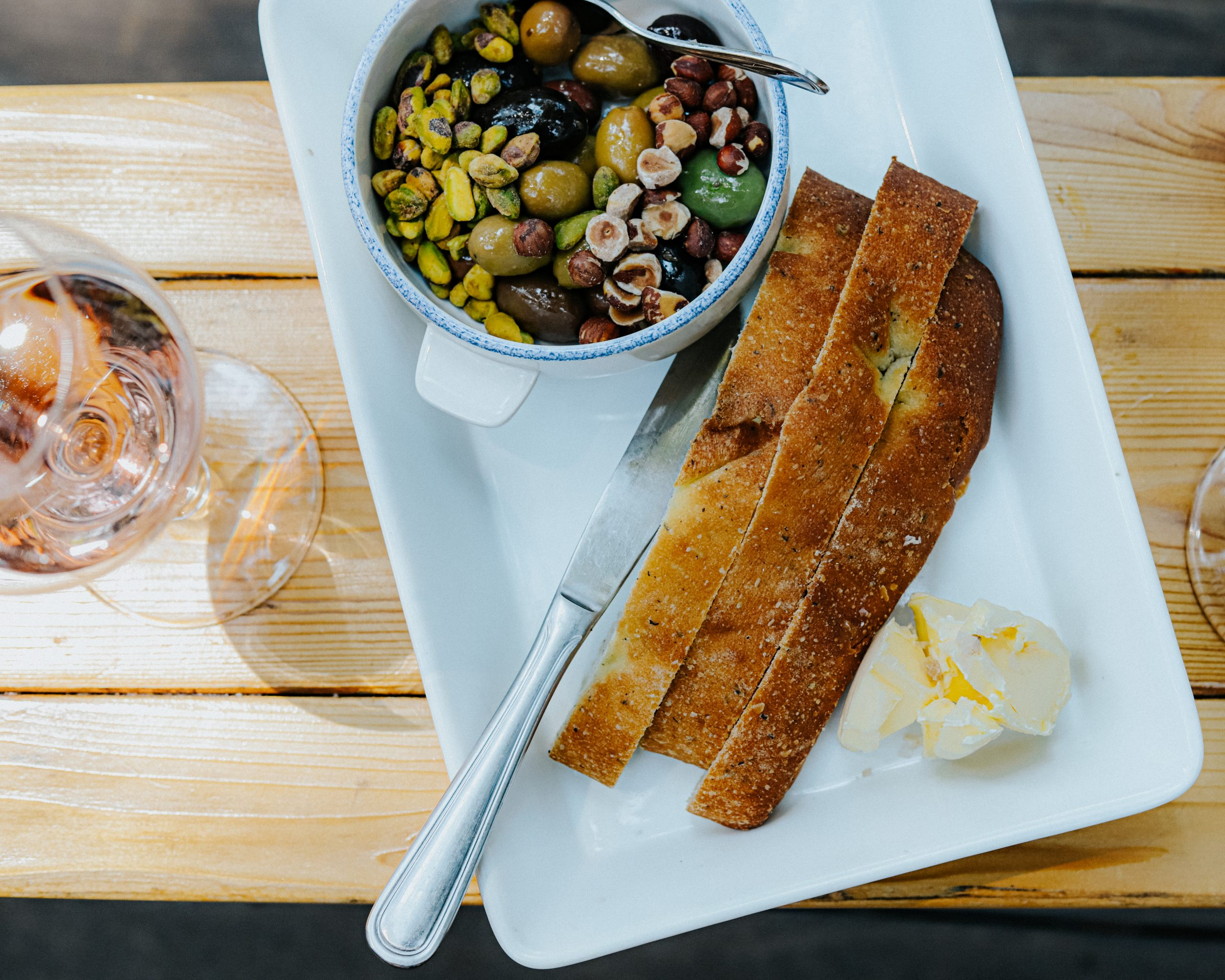 Plate of sliced focaccia next to a bowl of olives on a picnic bench
