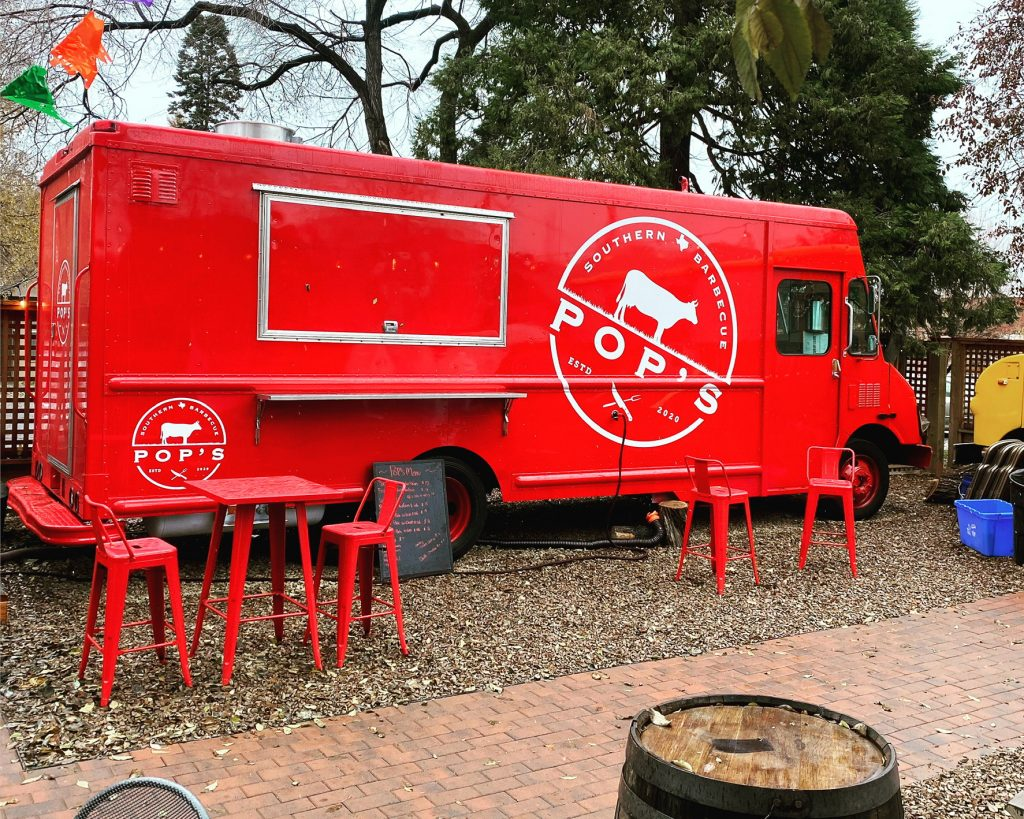 Large red food truck with Pops Southern BBQ logo, parked inside Bunk and Brew Bend Oregon.