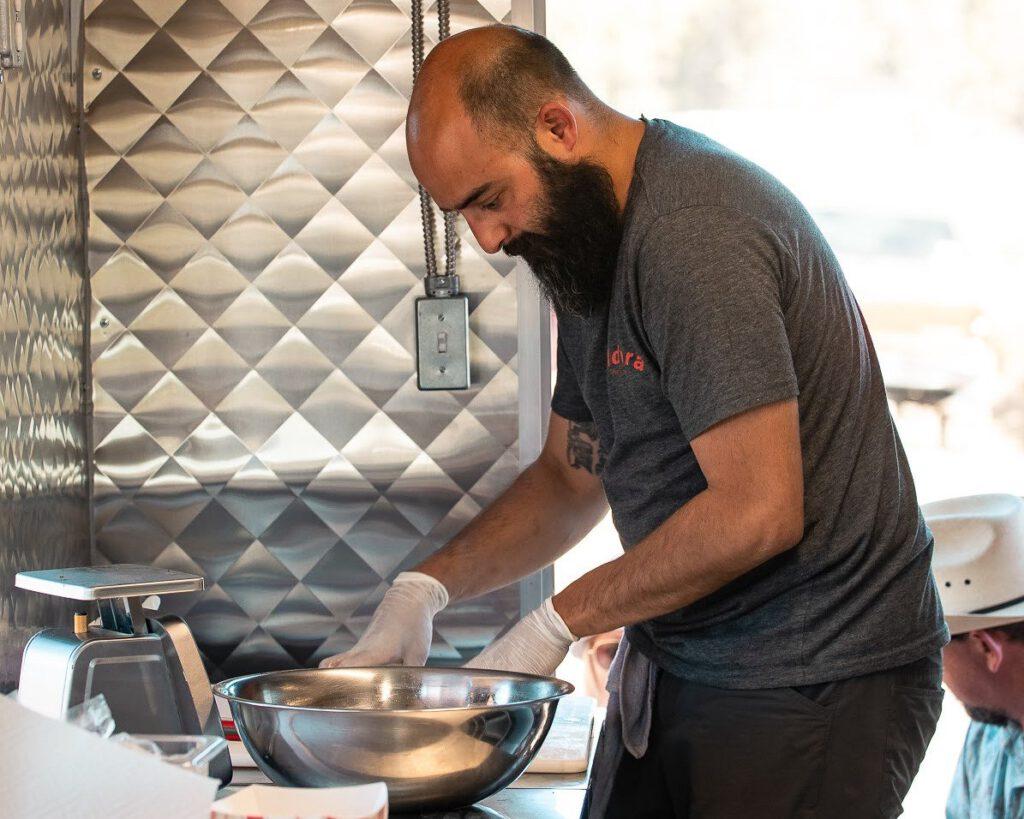 John Guzman seasons meat with dry rub.
