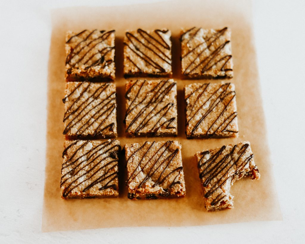 9 cookie bars drizzled in chocolate, cut into squares with bite taken out of one