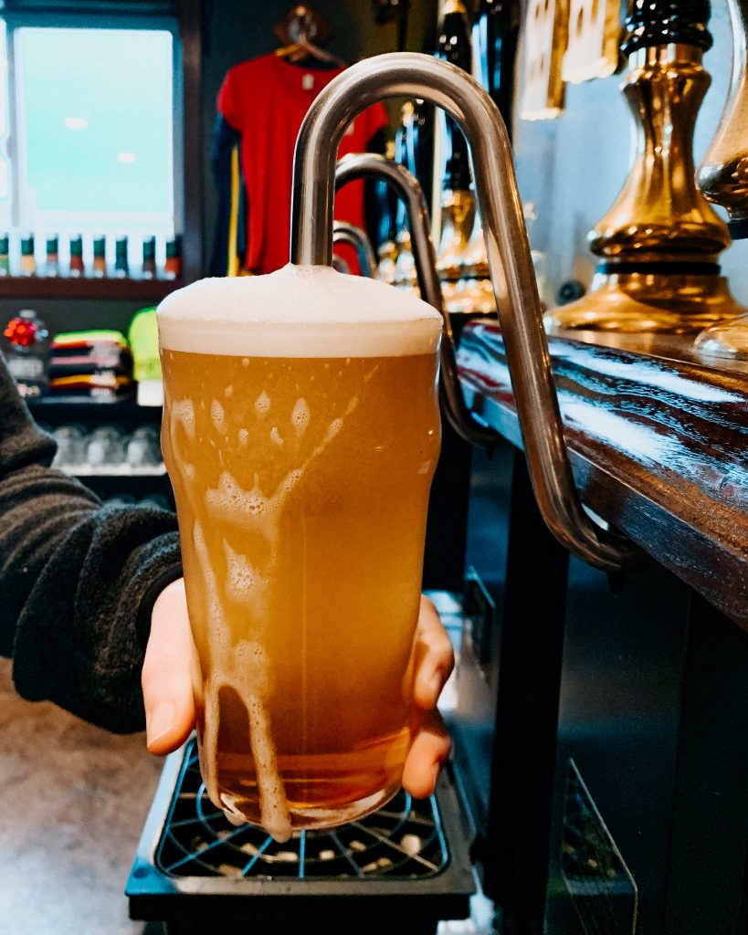 Hand pump pouring ale into chilled pint glass