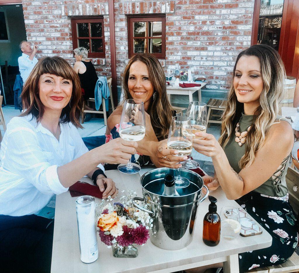 Three women cheers glass of Elixir chardonnay
