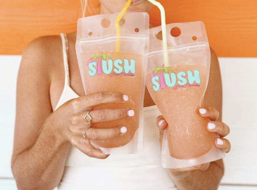 Woman holds two pouches of boozy slushie from Boss Rambler Beer Club in Bend Oregon